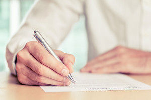 Businessman signing a document. Tinted photo, shallow depth of field.