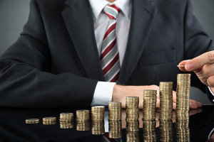 Businessman Placing Coin Over Stack Of Coins