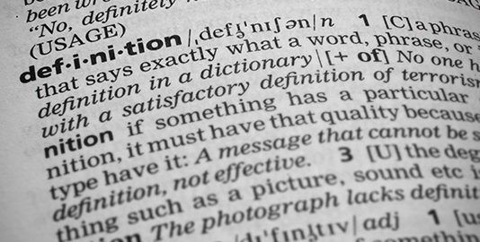 Closeup shot of the word definition in a dictionary. Page curves and has a vignetting or edge burn effect where the corners are darker. Focus is on the word definition.