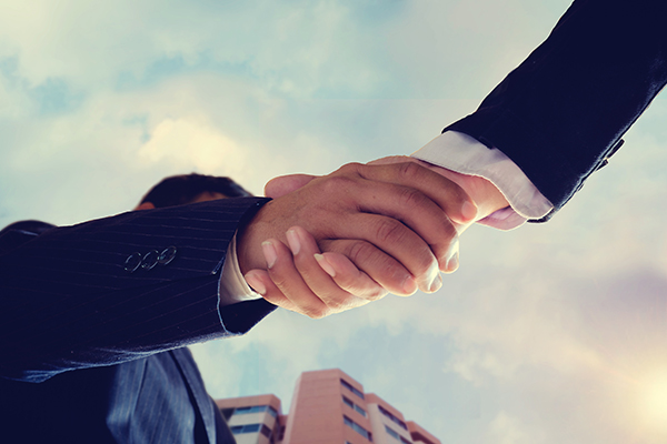 Worm eye view shot of businessmen handshaking.acquisition concept.